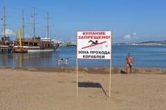 Underteckna ingen simning! Zonplanera passagen av skepp på bakgrund av folk som badar på hytten i Gelendzhik Royaltyfri Fotografi