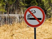 Underteckna inget - röka på bakgrunden av skogen och torrt gräs och träd royaltyfri bild