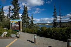 Underteckna längs Yukon River de välkomnande besökarna till Whitehorse Royaltyfri Bild