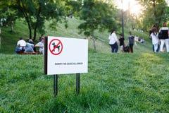 Underteckna med inskriften som förbjuder hunden som går i en parkera med grönt gräs fotografering för bildbyråer