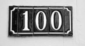Underteckna med numret 100 gjorde med glansiga tegelplattor Arkivfoton