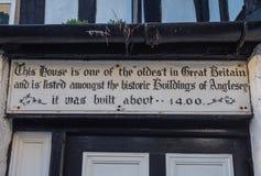Underteckna på det äldsta huset i Anglesey Wales Royaltyfri Foto