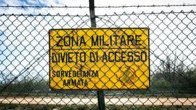 Underteckna som läser in den italienska militära zonen, inget tillträde, beväpnad bevakning Arkivbild