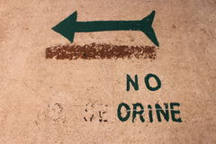 Underteckna som säger att 'inte kissa' i spanjor med en grön pil Royaltyfri Fotografi