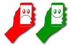 underteckna telefonen i min hand som är röd och som är grön med smileyframsidan Arkivbilder