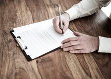 Undertecknande avtal eller dokument för man på träskrivbordet royaltyfria foton