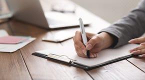 Undertecknande avtal för affärskvinna som i regeringsställning arbetar arkivfoto