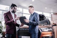Undertecknande avtal för affärsman, medan köpa den nya bruna halvkombibilen royaltyfri fotografi