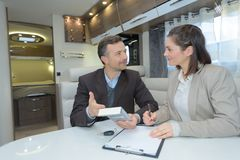 Undertecknande avtal för affärsman medan partner som ser honom Arkivfoton