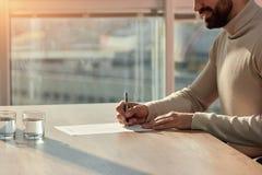 Undertecknande avtal för Berded man på kontorsskrivbordet royaltyfria foton