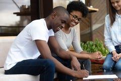 Undertecknande avtal för lyckliga afrikansk amerikanpar i kafé royaltyfri fotografi