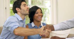 Undertecknande avtal för lyckliga par med fastighetsmäklaren arkivfilmer