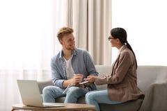 Undertecknande avtal för ung man med det kvinnliga försäkringmedlet arkivbild
