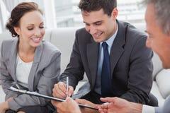 Undertecknande avtal för affärsman, medan hans partner ser honom Arkivbild