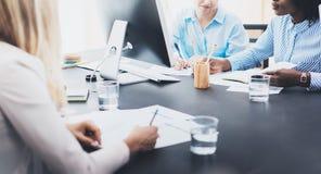 Undertecknande dokument för härlig blond kvinna på arbetsplats i modernt kontor Grupp av flickacoworkers som tillsammans diskuter Arkivfoton