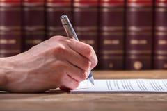 Undertecknande dokument för mänsklig hand royaltyfri bild