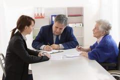 Undertecknande försäkringavtal och donation för farmor till hennes gran arkivfoton