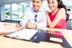 Undertecknande försäljningsavtal för asiatiska par för bil Royaltyfri Foto