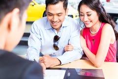 Undertecknande försäljningsavtal för asiatiska par för bil Arkivbild