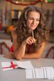 Undertecknande julvykort för fundersam hemmafru i kök Royaltyfri Bild