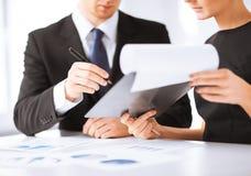 Undertecknande papper för affärsman och för affärskvinna Arkivfoton