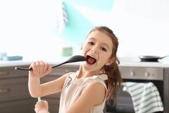 Undertecknande sång för gullig liten flicka in i skeden fotografering för bildbyråer