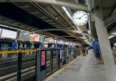 Undertecknar den dubbla sidklockan för den Skytrain järnvägsstationvisningen och en lång plattform med pilar i-ut riktning till v royaltyfri fotografi