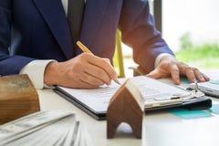 Undertecknar den hem- köpekontraktet för begreppet, affärsmän ett hus p Royaltyfri Bild