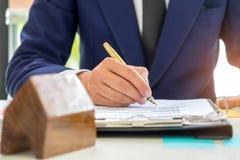Undertecknar den hem- köpekontraktet för begreppet, affärsmän ett hus p Arkivbild