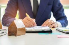 Undertecknar den hem- köpekontraktet för begreppet, affärsmän ett hus p Royaltyfri Foto