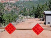 Undertecknar den röda reflektorn för varning att hänga på den blockerande vägbarriären Arkivfoton