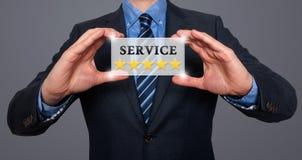 Undertecknar det hållande vita kortet för affärsmannen med stjärnor för service fem, Gre Royaltyfri Bild