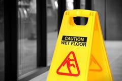 Undertecknar det våta golvet för guling in ett hall, selektiv färg Arkivfoton