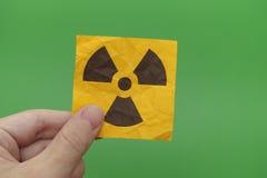 Undertecknar hållande utstrålningsvarning för personen in hans hand arkivbild