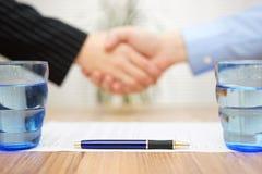 Undertecknat avtal med handskakningen i suddighet, fokus på penna Arkivfoto