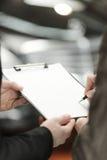 Underteckning av en överenskommelse för bilbilförsäljning. Närbildfors av avtalet Arkivfoto