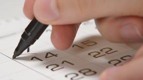 Underteckning av en dag för valentin` s på en kalender vid röd pennhjärta arkivfilmer