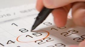 Underteckning av en dag på en kalender vid pennan Arkivfoto