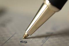 Underteckning av en kontroll för personliga finanser Arkivfoto