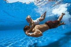 Undervattens- bild av en man och en flicka royaltyfri foto