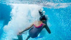 Undervattens- bild av ton?rs- flicka som tv? hoppar och dyker i simbass?ng p? idrottshallen royaltyfri foto