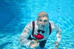Undervattens- dykning för stilig brudgum som ger en röd rosblomma arkivfoton
