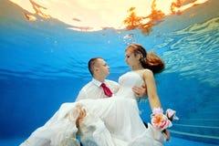 Undervattens- förälskelse en man som rymmer hans brud i en bröllopsklänning på bakgrunden av en tropisk solnedgång och blickar på Royaltyfri Foto
