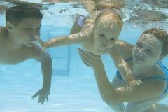 Undervattens- familj i simbassäng Royaltyfria Foton