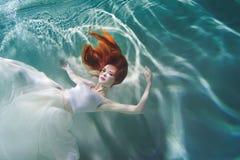 Undervattens- flicka Härlig rödhårig kvinna i en vit klänning som simmar under vatten fotografering för bildbyråer
