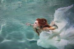 Undervattens- flicka Härlig rödhårig kvinna i en vit klänning som simmar under vatten royaltyfri bild