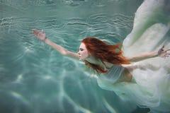 Undervattens- flicka Härlig rödhårig kvinna i en vit klänning som simmar under vatten royaltyfri fotografi