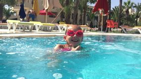 Undervattens- flickatonåringsimning och dykning, i att sväva pölen i semesterorthotell stock video