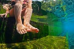 Undervattens- foto av kal fot för barn i naturlig simbassäng Royaltyfria Bilder