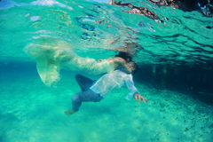 Undervattens- härlig älskvärd kyss för brud och för brudgum Royaltyfria Foton